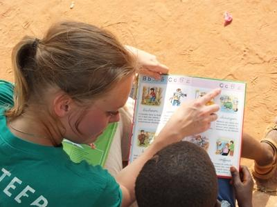 Projects Abroad volunteer reads with a Togolese child at a care center in Lomé.