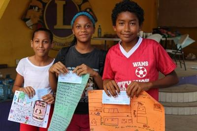 Projects Abroad volunteer with local children and their artwork in Belize, Central America.