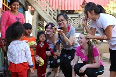Teenage volunteers, working on a Care & Community project in Cambodia, enjoy some time with the children from their placement
