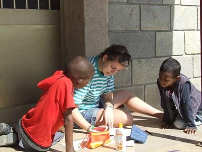Teen volunteer paints with kids at care placement on the Care & Community project in Ethiopia