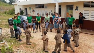 Jamaican children take part in a physical activity outdoors with volunteers.