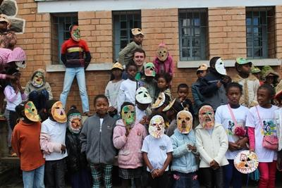 Projects Abroad volunteer with a group of local children and their arts and crafts in Madagascar.