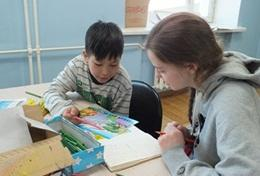 A High School Special Care & Community volunteer assists a young child with an activity in Mongolia.