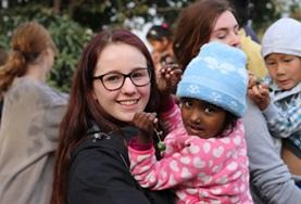 A Care & Community High School Special volunteer in Nepal holds a child at her placement.