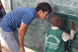 In Senegal, a Care & Community High School Special student volunteer helps a boy as he writes on the blackboard.