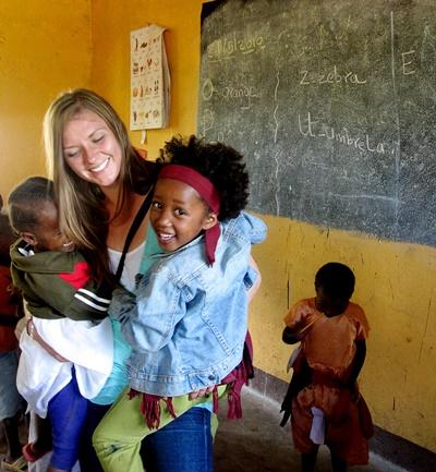 Volunteer holds children in a care center on the Care & Community volunteer project in Tanzania