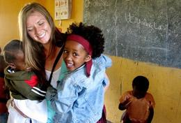 A volunteer hugs children on her Care & Community High School Special in Tanzania.