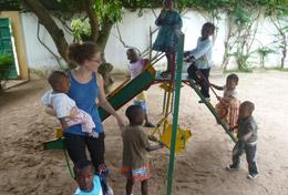 A volunteer on the Togo Care & Community High School Special plays with children on the playground.