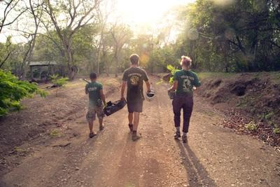 Projects Abroad satff and volunteers carry trees after a long day of planting saplings in Costa Rica
