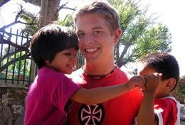 A volunteer plays with children on the playground as part of his Care & Spanish High School Special in Argentina.