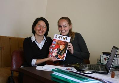 Teen volunteers in Romania pose with their published magazine on the Journalism project