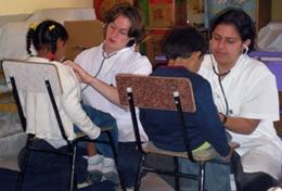 High School Special Medicine volunteers in Bolivia check young children's heartbeats.