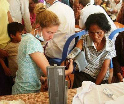 Teen volunteer in Cambodia checks an elderly woman's blood pressure on a Public Health project