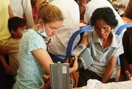 A High School Special student in Cambodia checks a woman's blood pressure on the Public Health Project.