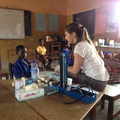 Projects Abroad Medicine High School Special volunteer assists with medical checks at a school in Ghana, Africa.