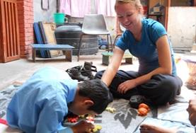 A student on the Physical Therapy High School Special in Nepal works with a young boy at her placement.