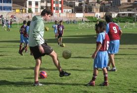 Volunteer on the Sports project coaches young boy in soccer overseas