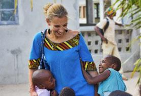Volunteer on a Care project plays outside with children in Africa