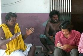 A volunteer on the Intern Abroad in Journalism Project interviews men for her story.