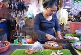 A local entrepeneur prepares food at her stall funded by the Microfinance Project.
