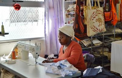 Woman sews clothing in her small business where interns work in South Africa