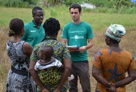 A microfinance intern volunteer gives local business women advice during his project in Ghana.