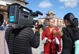 A monk in Mongolia is interviewed by interns on the Journalism Project.