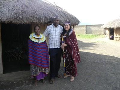 Volunteer with staff and local learning Swahili in a traditional village