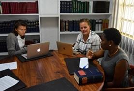 Two volunteers on the Human Rights Internship in Tanzania discuss a case with their supervisor.