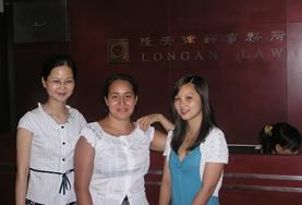 Two volunteers on the International Law Internship in China take a photo with their supervisor.