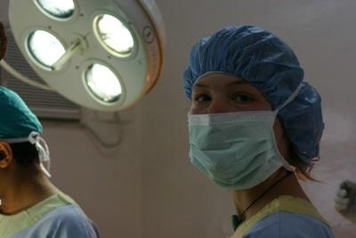 Volunteer on the dentistry project dressed in scrubs observing dental surgery in Nepal