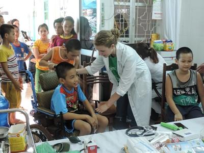 Projects Abroad Dentistry intern helps a Vietnamese child during a community outreach in Hanoi, Asia.