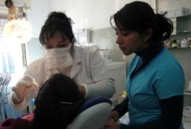 A volunteer observes her supervisor as she performs a dental procedure on a patient in Argentina.
