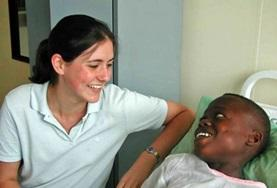 A student on her dentistry internship in Ghana sits with a patient.