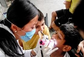 A dentist in Mexico examines a child's teeth while another child observes.