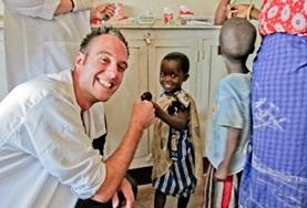 A dental intern in Tanzania fist-bumps a young child after a dental appointment in Tanzania.
