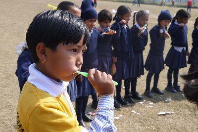 Interns teach Nepalese children how to care for their teeth at a medical outreach.