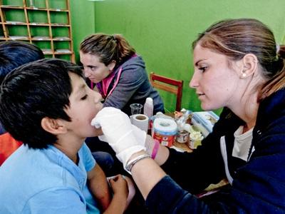 A Peruvian child receives treatment from a medical intern at an outreach