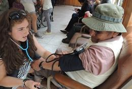 A volunteer and supervisor check a patient in Bolivia on the Medical Internship Abroad.