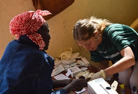 A student on the medical internship in Kenya checks a woman's vital signs.