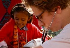 A medical intern in Nepal checks a young girl's vital signs at a medical outreach.