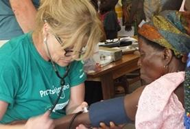 A medical intern in Togo checks an older woman's blood pressure during a medical outreach.