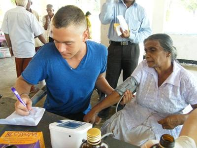 Nursing volunteer records the blood pressure of an elderly woman in an outreach in Sri Lanka