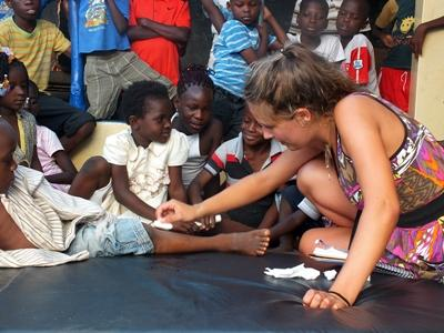 Nursing volunteer dresses a child's wounds in Togo