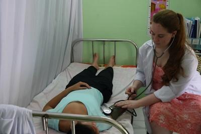 Projects Abroad intern at a Nursing placement learns how to take vital signs on a fellow intern in Vietnam.