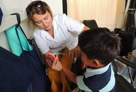 A Nursing volunteer in Bolivia assists a young boy at her placement.