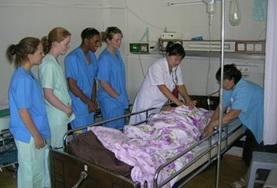Nursing volunteers in Mongolia observe a procedure by a head nurse.
