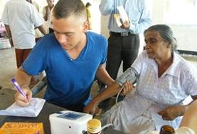 A volunteer on the Nursing Internship in Sri Lanka takes a woman's vital signs.