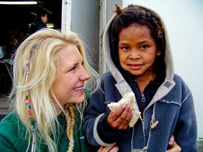 A female intern watches over a child eating bread in a South African township.