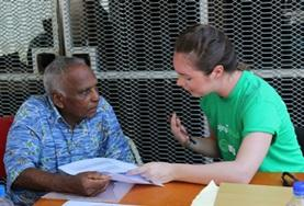 A Nutrition volunteer in Fiji explains a healthy diet to an older man.